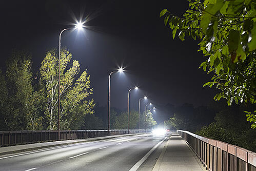 Light poles lining a street on a dark night.