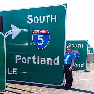 Navjoy employee stands next to large highway traffic signs