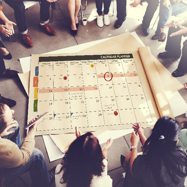 Team of professionals surrounding a calendar and selecting deadlines for tasks to be completed by