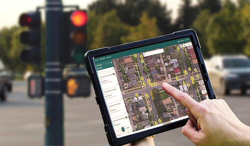Hands of a field technician holding an iPad and using NueGOV software to record data about a traffic signal at an intersection.