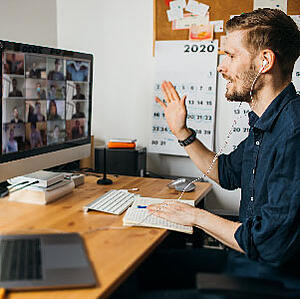 Young man attending a virtual meeting from his office desk with employees he works with