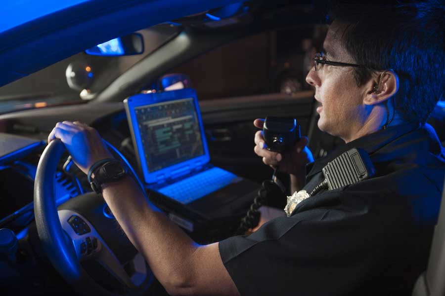 An officer speaking into a radio while sitting in a cruiser.